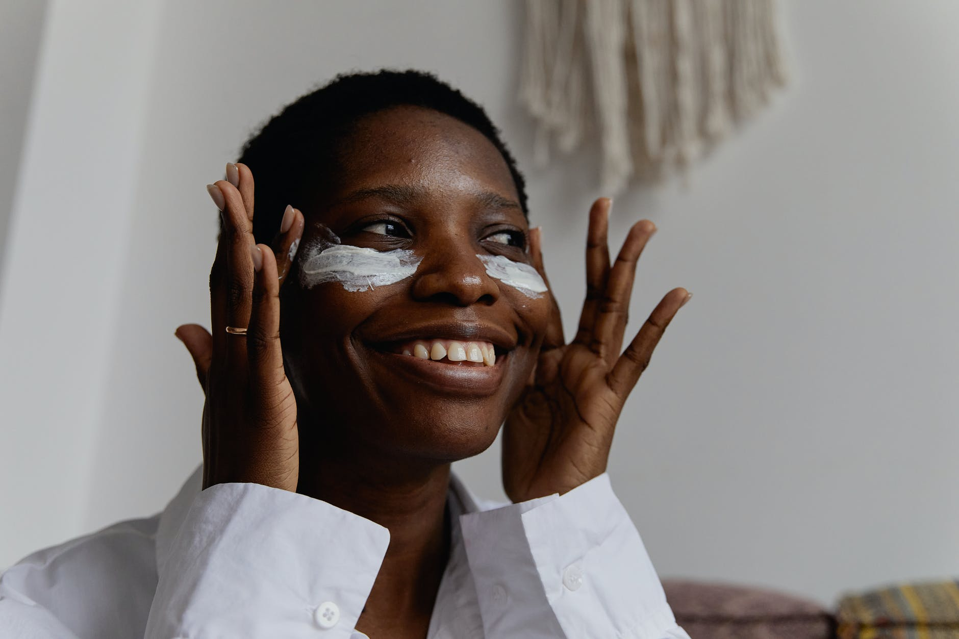 Woman smiling and putting face cream   Source: Pexels