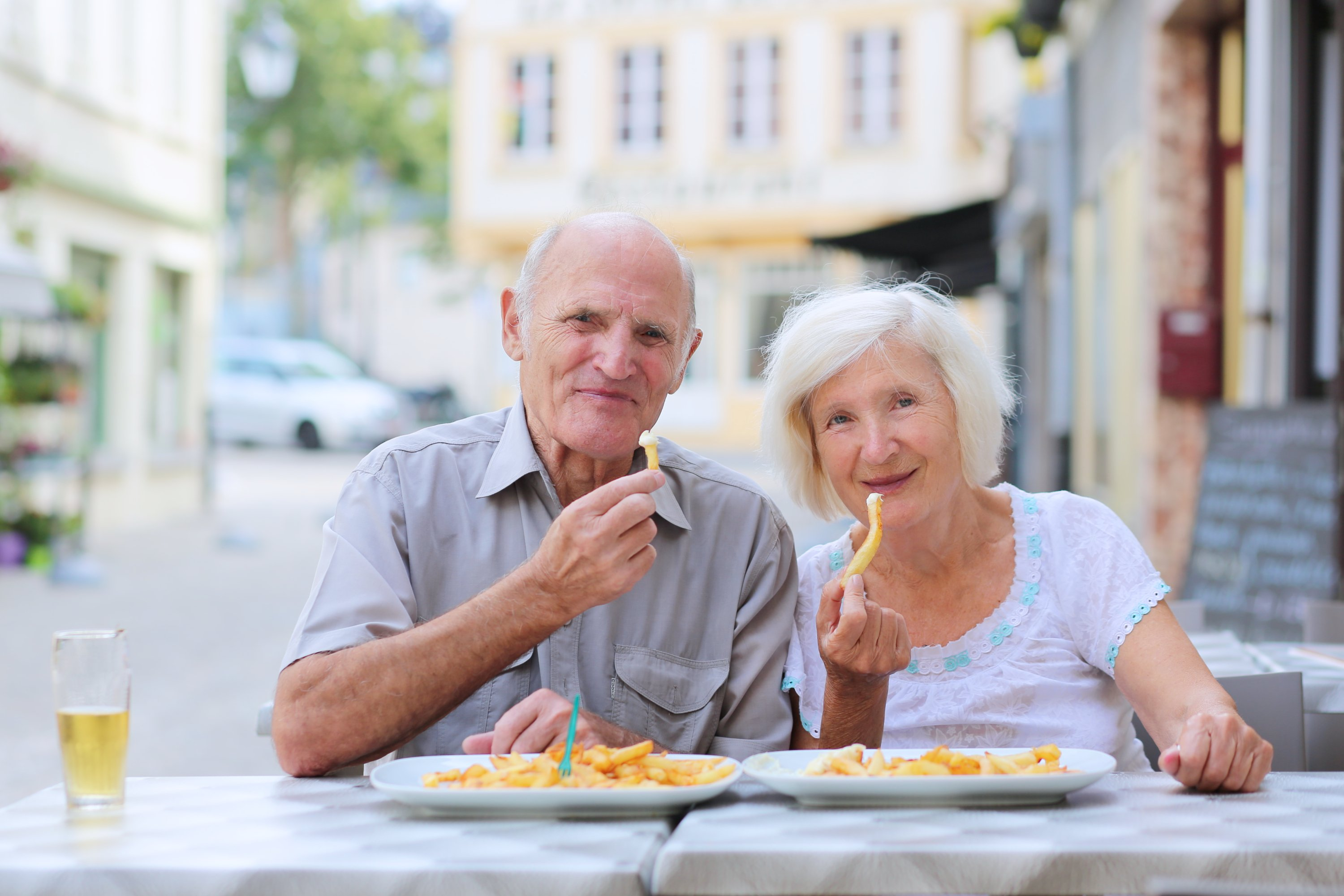 Happy active senior couple enjoying time together eating belgian french fries in outdoors street cafe on a summer day in typical European town | Photo: Shutterstock.com