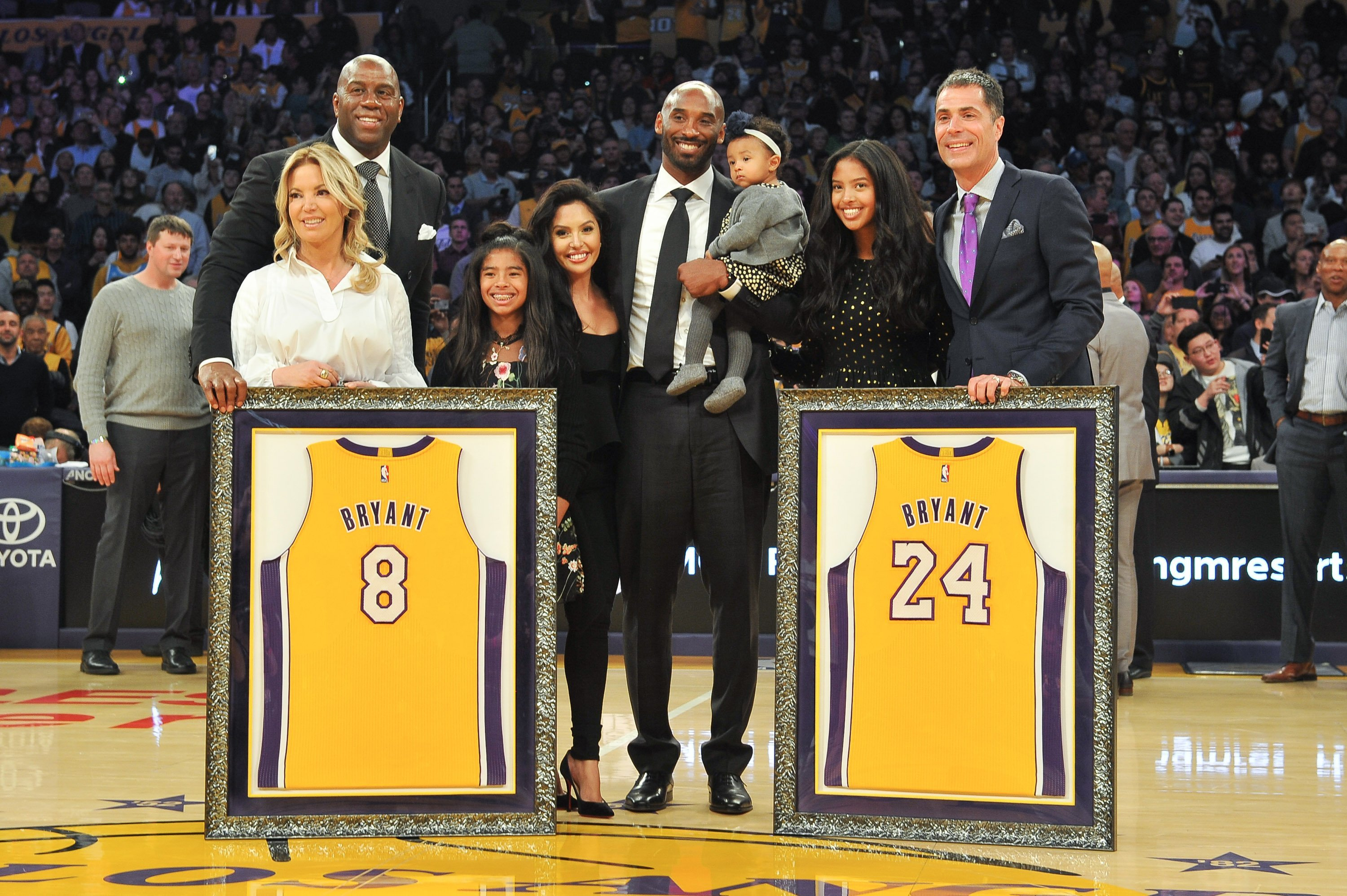 Magic Johnson, Jeanie Buss, Kobe Bryant, Vanessa Bryant, their daughters, and Rob Pelinka during Kobe Bryant's jersey retirement ceremony  at Staples Center on December 18, 2017  | Photo: GettyImages