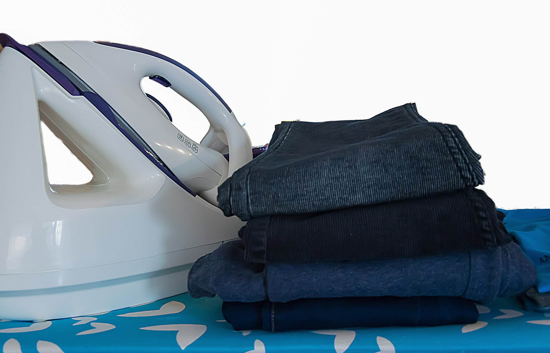 A pile of ironed clothes next to an iron. | Source: Michal_o79/Pixabay