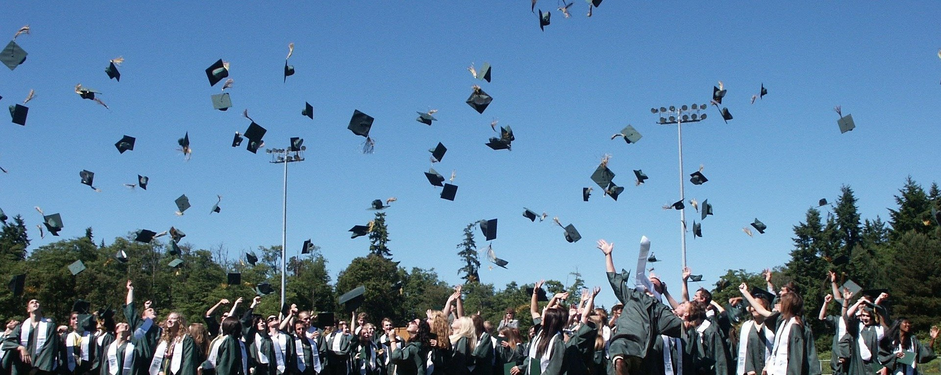 A bunch of high school graduates throw their graduation caps up in the air while celebrating outdoors | Photo: Pixabay/Gillian Callison