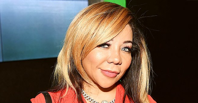 Tiny Harris Looks Unforgettable Showing Chest & Arm Tattoos in Black Dress with a Deep Neckline