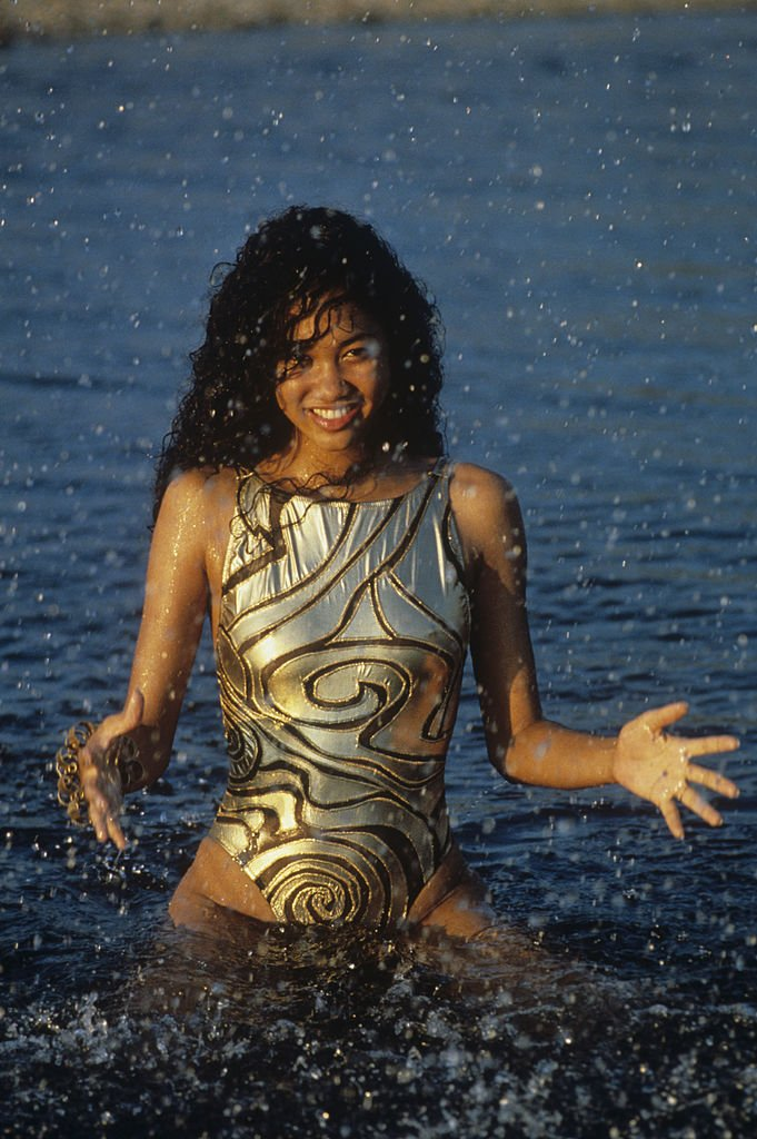 Kimora Perkins on August 12, 1990 in a golden swimsuit, in the water | Photo: Getty Images
