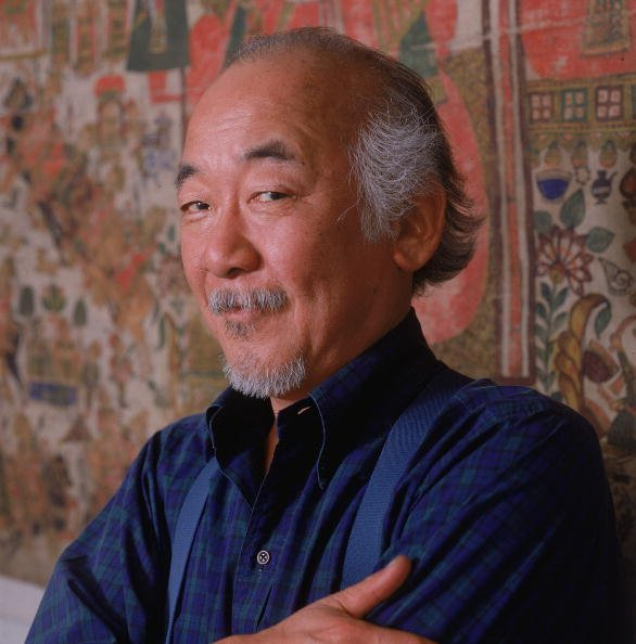 Portrait of American actor Pat Morita standing against a tapestry | Photo: Getty Images