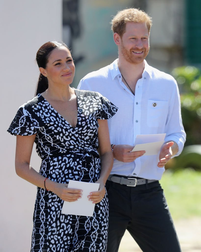 Meghan Markle et le prince Harry, duc de Sussex, sourient en visitant un bureau de justice dans le canton de Nyanga. | Source : Getty Images