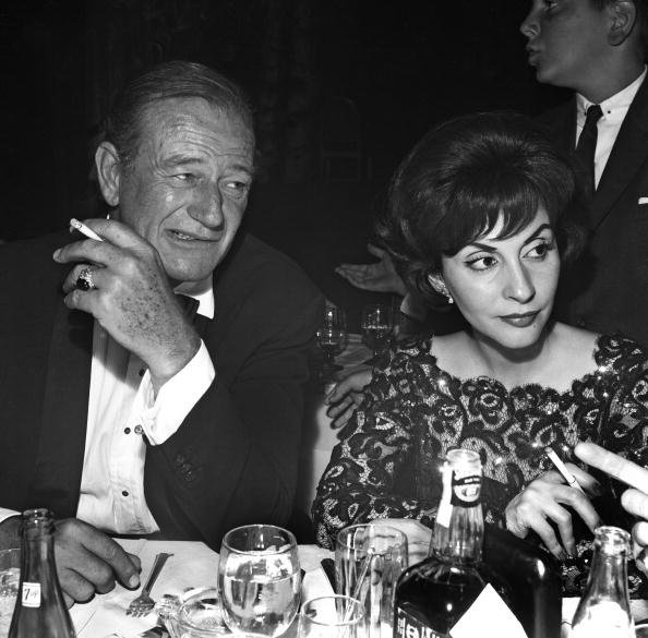 John Wayne and Pilar Palette on July 22 1961 at the Cocoanut Grove nightclub in Los Angeles, California. | Photo: Getty Images