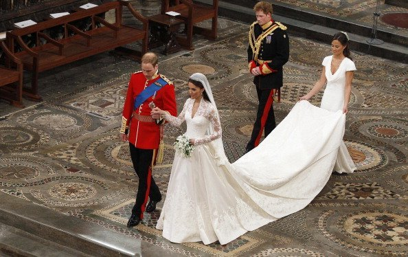 Prince William takes the hand of his bride Catherine Middleton, followed by Prince Harry and Pippa Middleton as they walk down the aisle inside Westminster Abbey on April 29, 2011, in London, England. | Source: Getty Images.