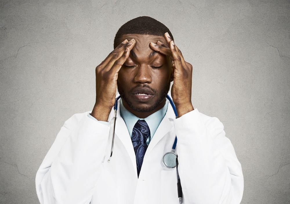 A doctor looks upset while running his temples. | Source: Shutterstock