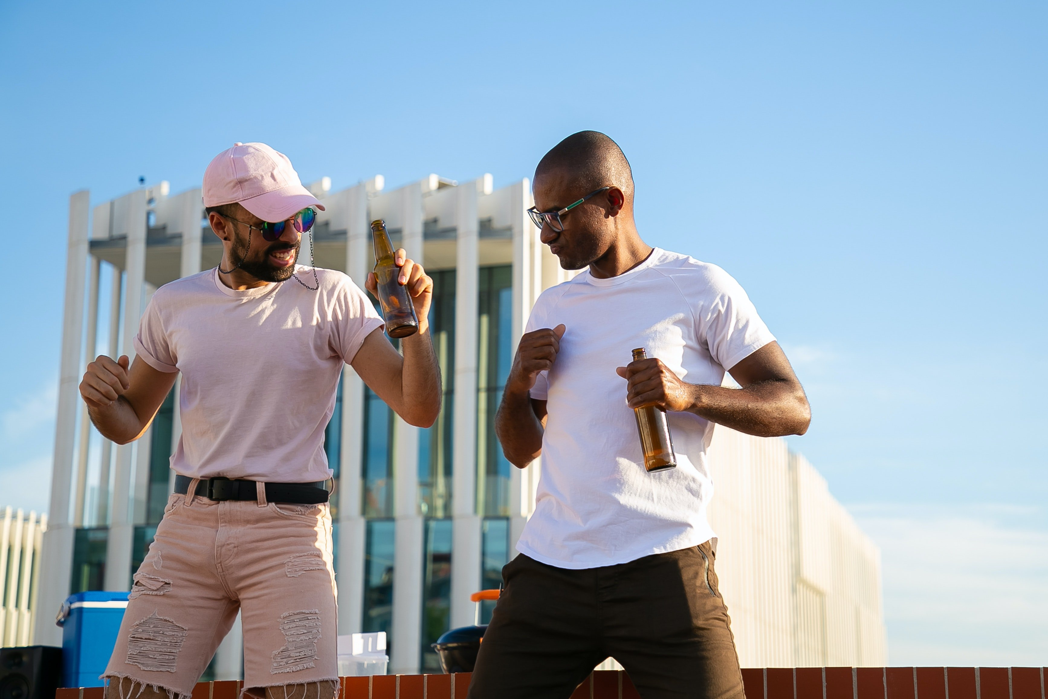 Two men drinking beer and dancing | Photo: Pexels