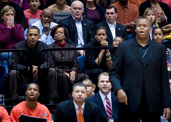 Barack Obama watches along with his mother in law Marian Robinson (2L) wife first lady Michelle Obama (3L) daughter Sasha Obama (3R), brother in law Craig Robinson (2R) and daughter Malia Obama (R) during a college basketball game at George Washington University November 28, 2009, in Washington, DC. | Source: Getty Images.
