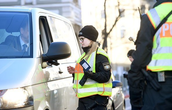 A policewoman checks a driver at a roadblock in Munich | Photo: Getty Images