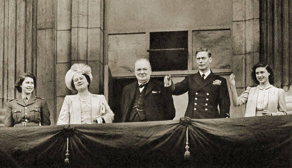 Winston Churchill with Princess Elizabeth, Queen Elizabeth, King George VI, and Princess Margaret, waving from the balcony of Buckingham Palace on VE-Day, 8 May 1945. | Source: Getty Images.