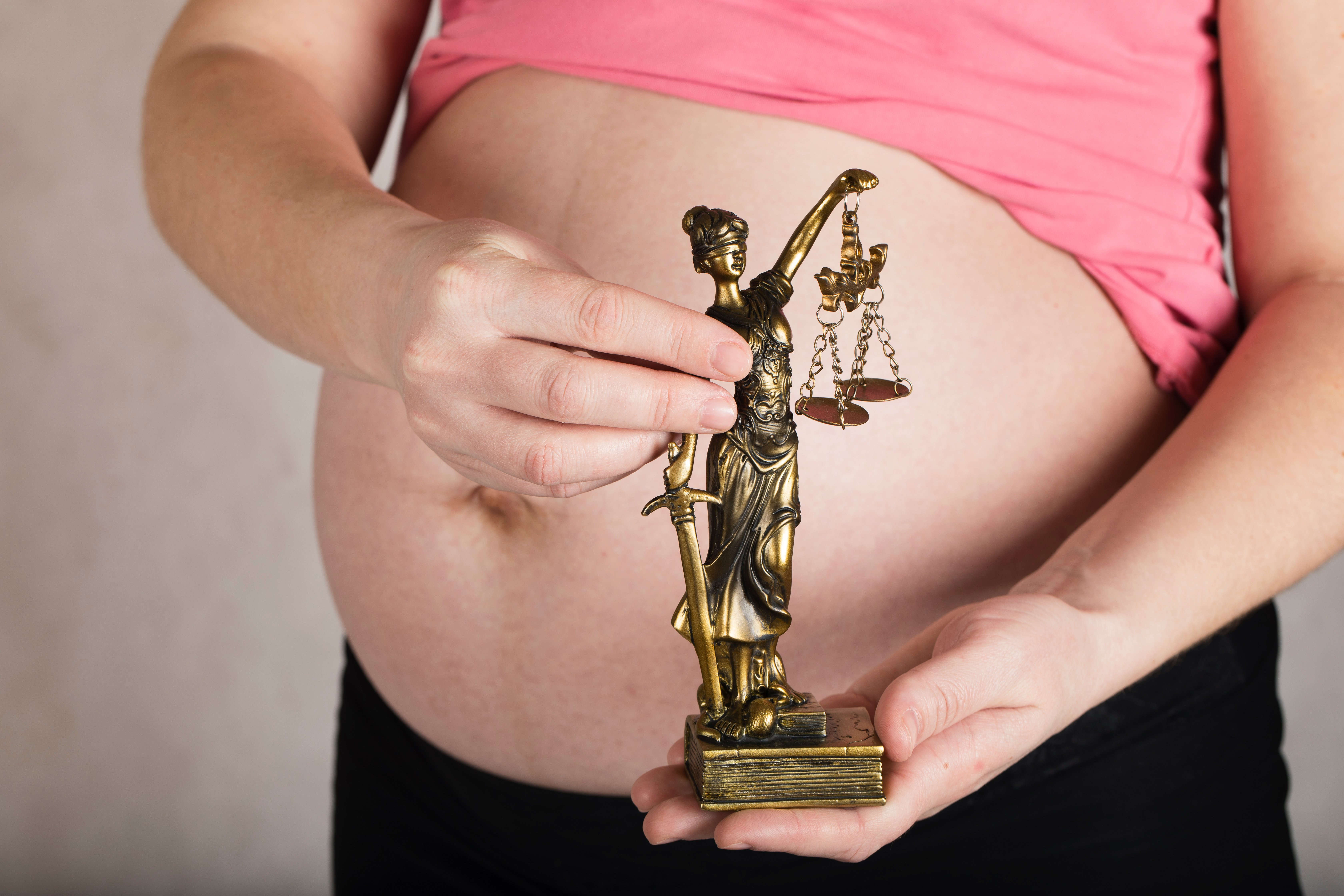 Woman with judge statue on pregnant stomach   Source: Shutterstock