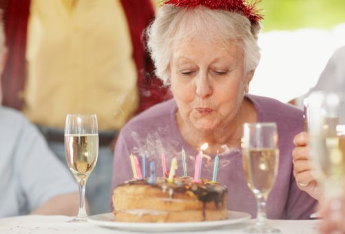 An elderly woman pictured blowing out the candles on a birthday cake | Photo: Getty Images