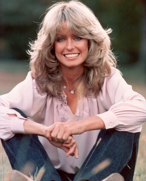 Undated photo of Farrah Fawcett smiling while sitting outdoors in blue jeans and a mauve blouse. | Photo: Getty Images