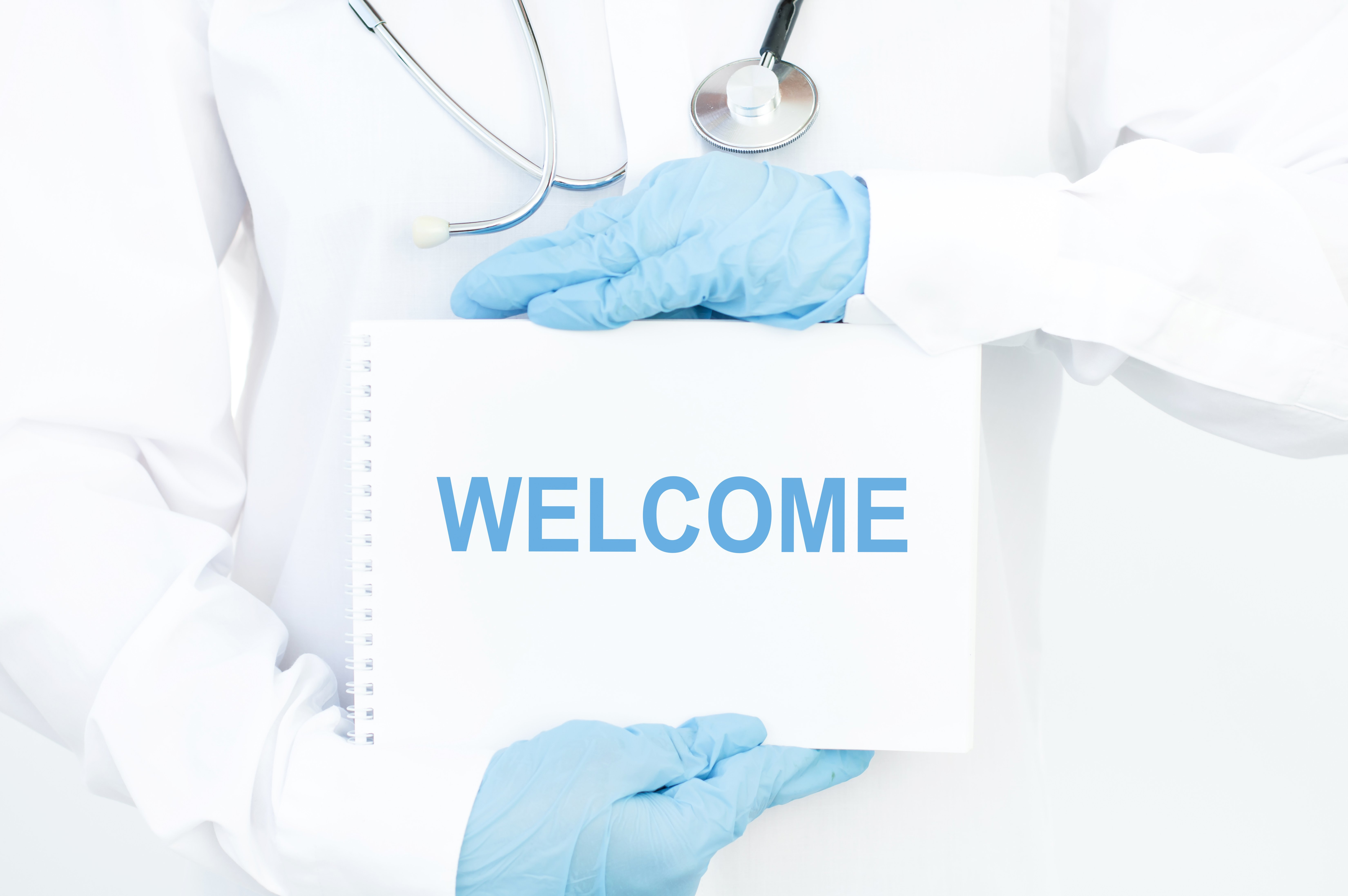 "Doctor wearing white coat and blue gloves holding a ""welcome"" sign. 