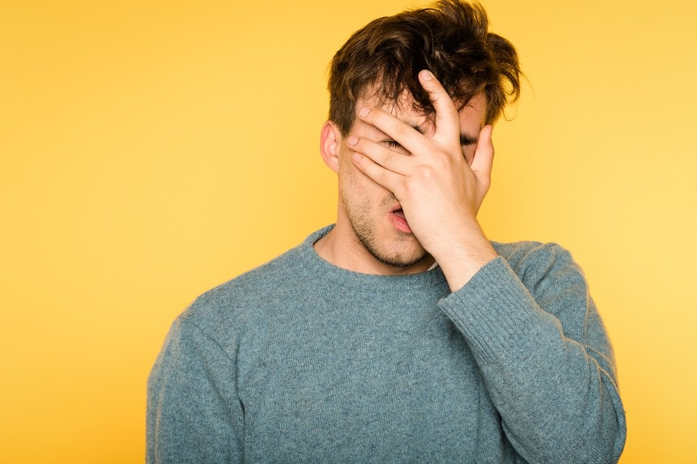 Man covering his face with one hand | Photo: Shutterstock/Golubovy