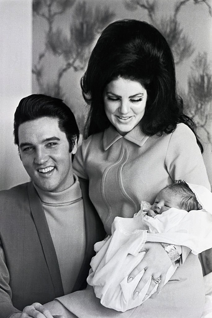 Elvis Presley and his wife, Priscilla Presley, smile as they hold their four-day-old daughter, Lisa Marie, before leaving Baptist Hospital, on February 07 1968, in Memphis Tennessee.