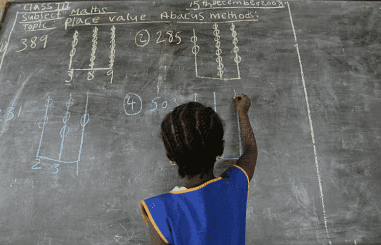 A young girl with braided hair, writing on a school blackboard in Kenema, Sierra Leone | Source: Getty Images (Photo by Ann Johansson/Corbis via Getty Images)