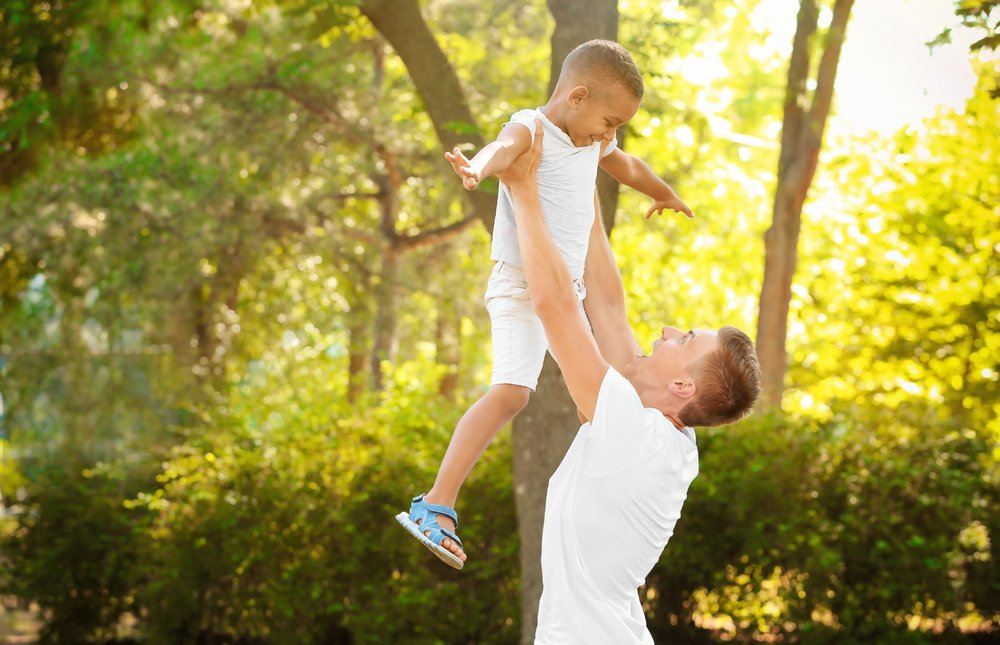 A young man playing with his adopted son. | Photo: Shutterstock