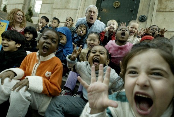 Robert Munsch and some kids make funny faces during story telling. | Photo: Getty Images