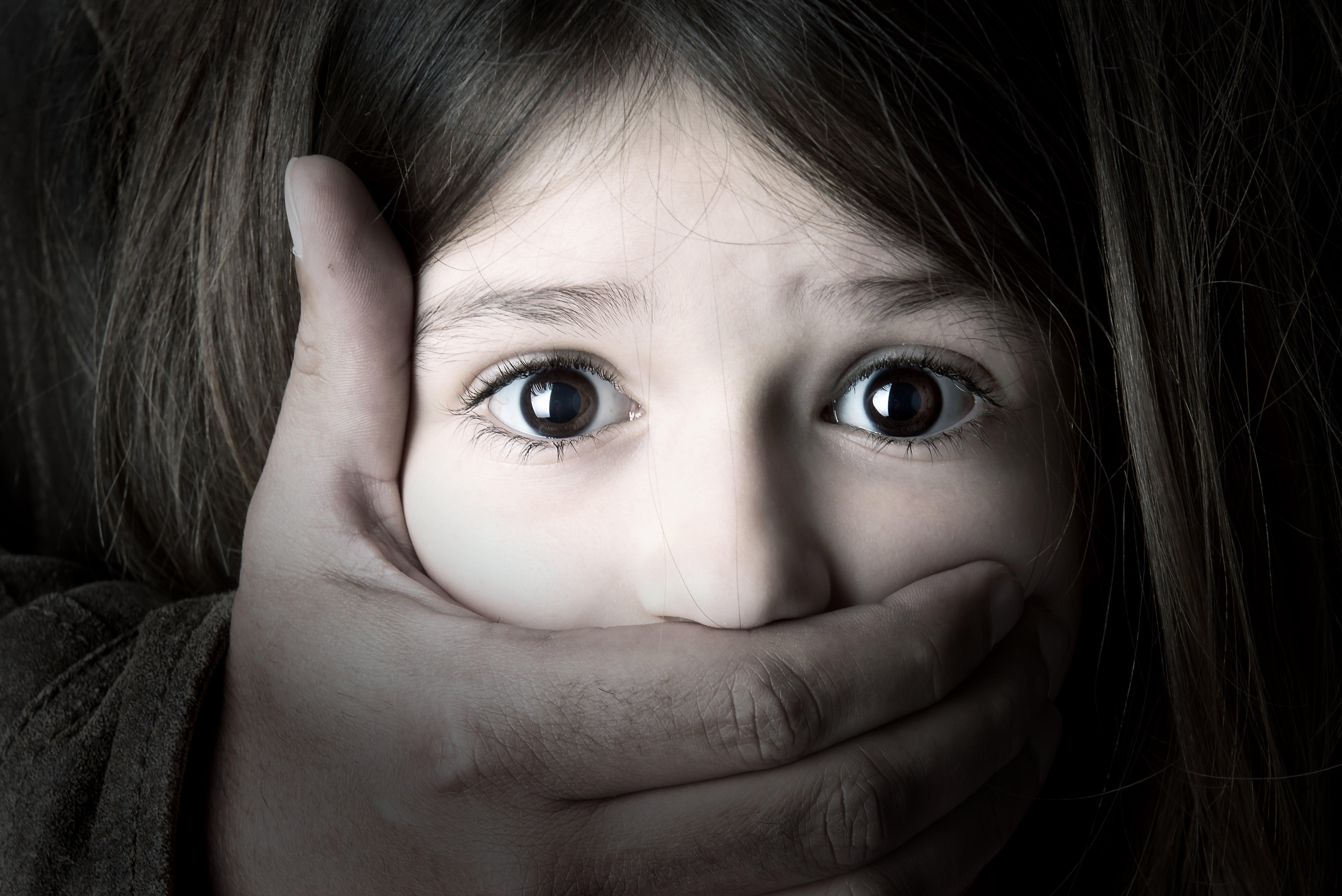 A una niña le tapan la boca con una mano. Fuente: Shutterstock