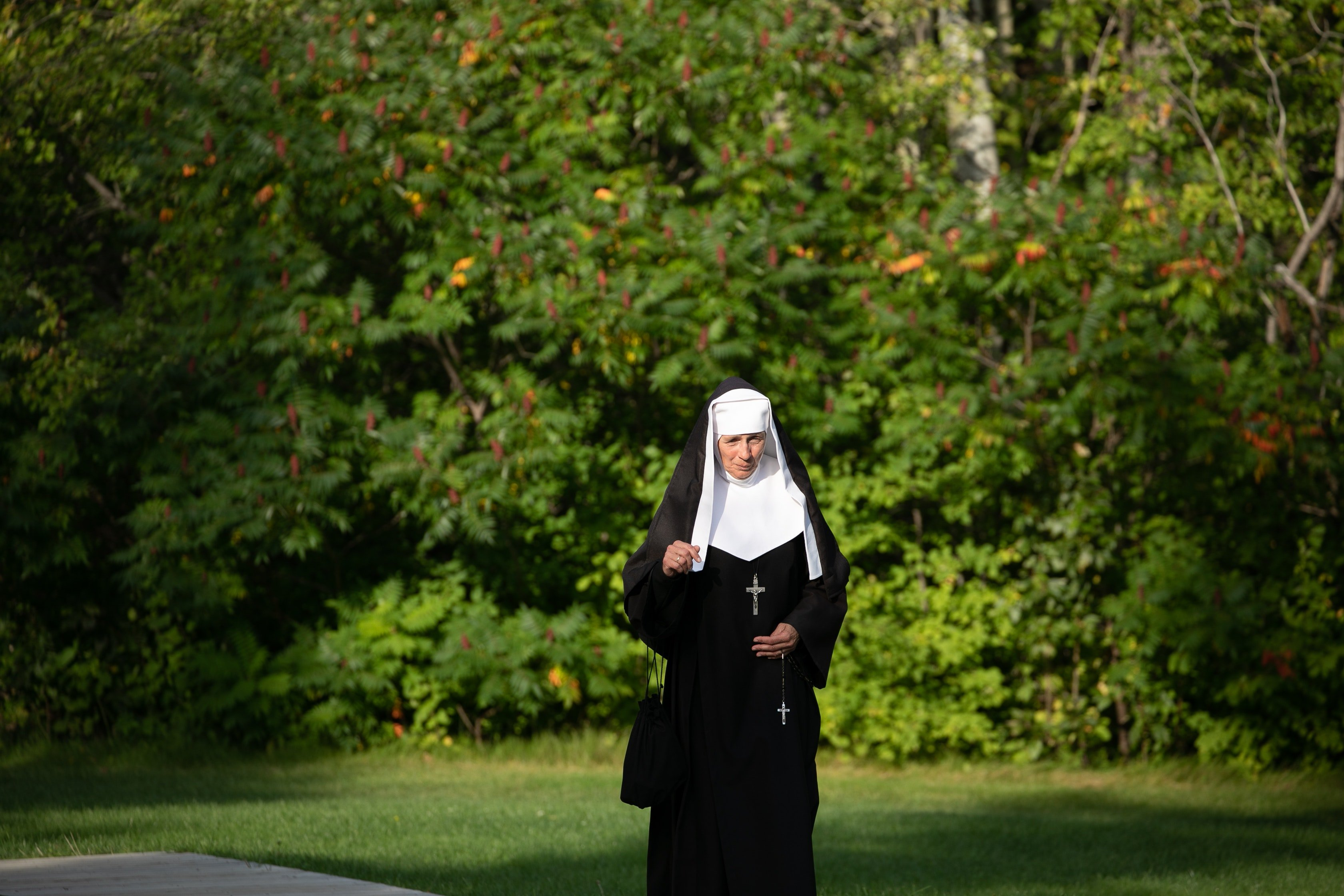 A nun holds a cross in her hand and walks down the street | Photo: Pexels/Mathieu Acker