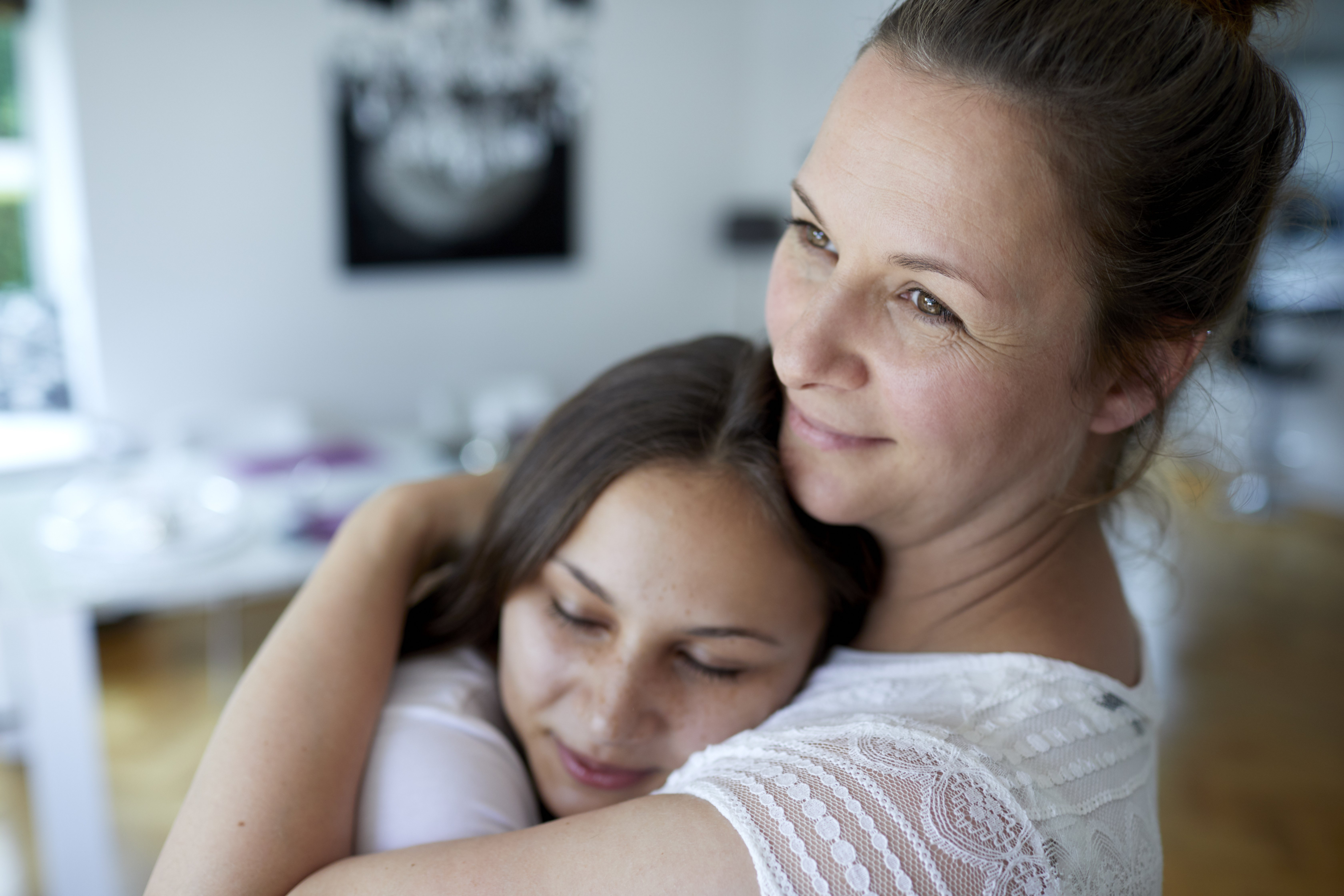 Mother and teenage daughter embracing at home|Photo: Getty Images