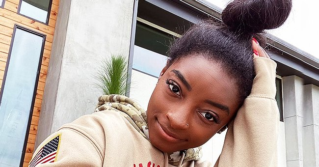 Simone Biles Shares a Cozy Picture Lounging in Her Backyard in a Hoodie and Tied Hair