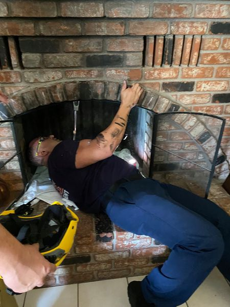 Fireman gets under the chimney to rescue stuck 18-year-old. | Source: Facebook/ Henderson Fire Department