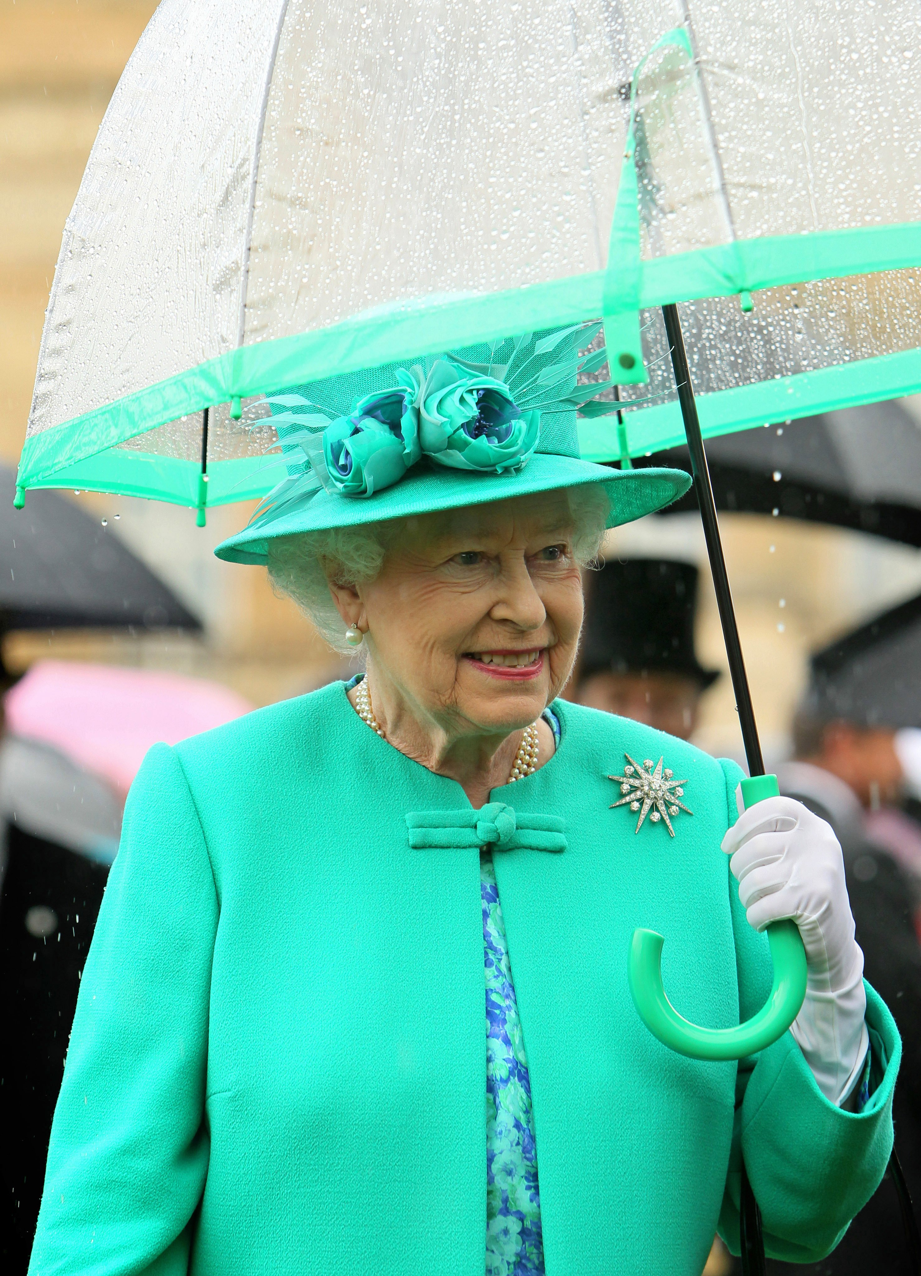 Queen Elizabeth II shelters from the rain under an umbrella at Buckingham Palace on July 19, 2011 in London, England | Photo: Getty Images