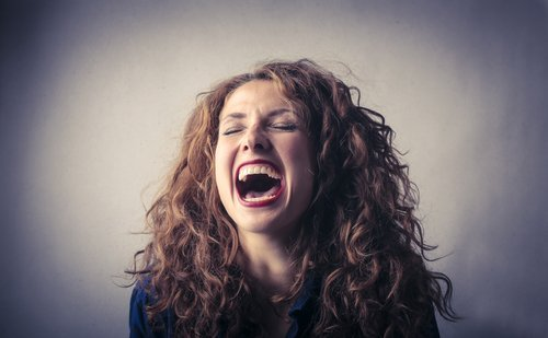 A woman laughing out loud. | Source: Shutterstock.