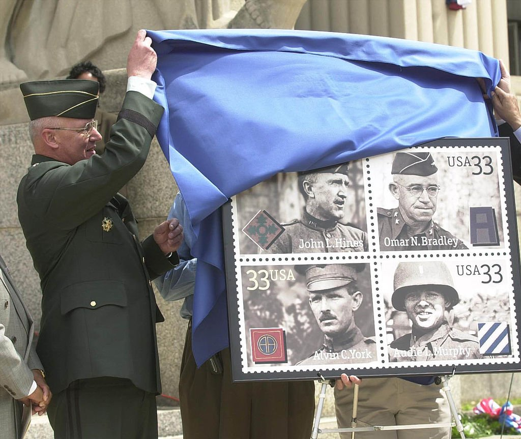 """Major General Thomas Plewes unveilsthe new """"Distinguished Soldiers"""" stamp thathonors Alvin C. York, John L. Hines, Audie L. Murphy, and Omar N. Bradley   Source Getty Images"""