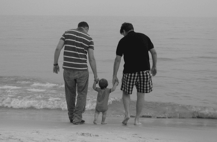 Dads taking their son on a walk on the beach | Source: Pixabay