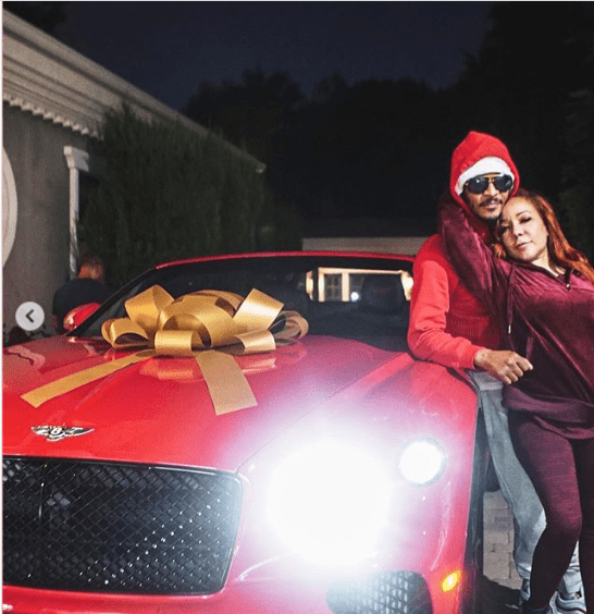 Tameka 'Tiny' Harris and T.I pose next to the red Bentley he gifted her on her birthday | Source: Instagram.com/majorgirl