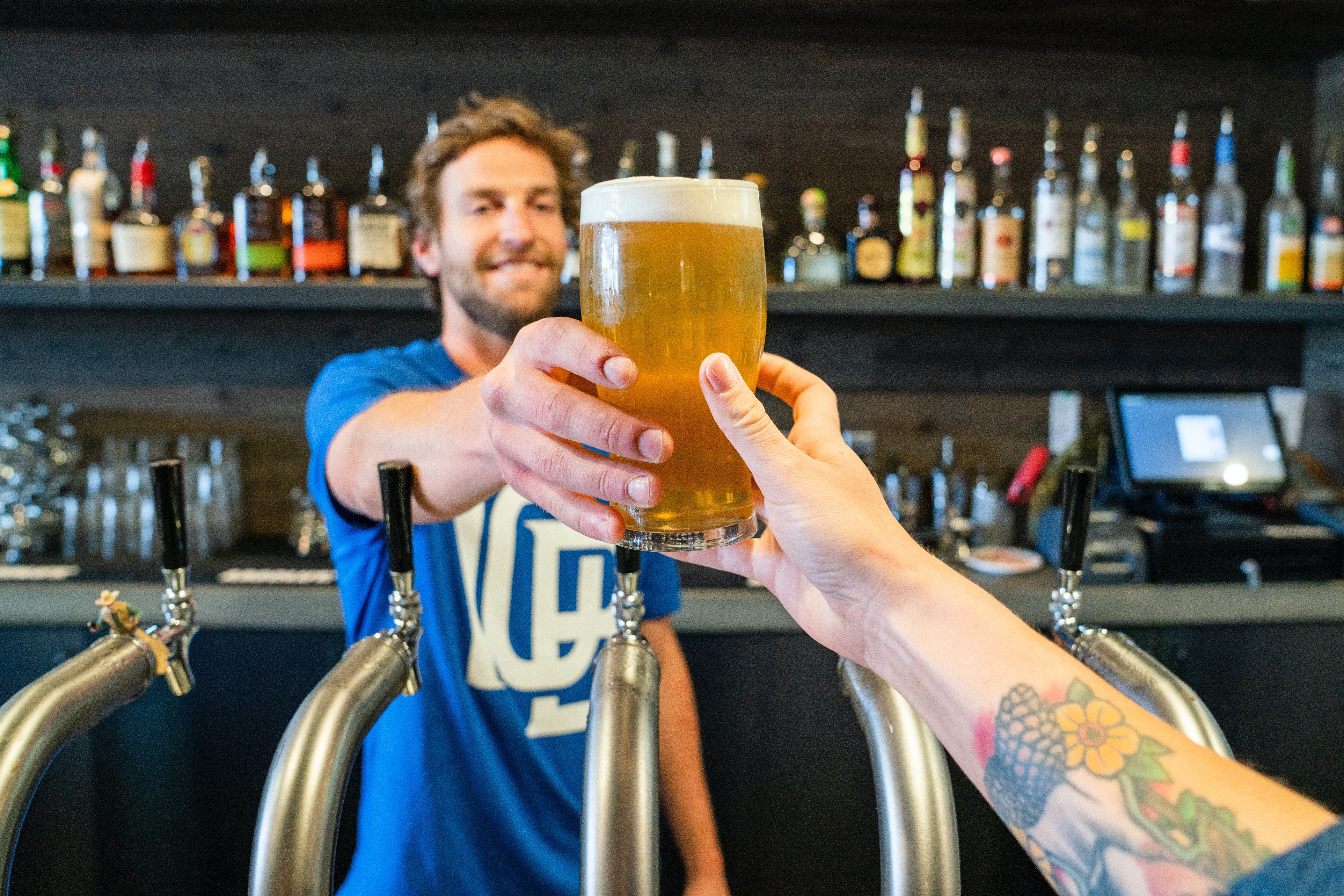 A bartender handing a beer over to a patron. | Photo: Pexels/ ELEVATE