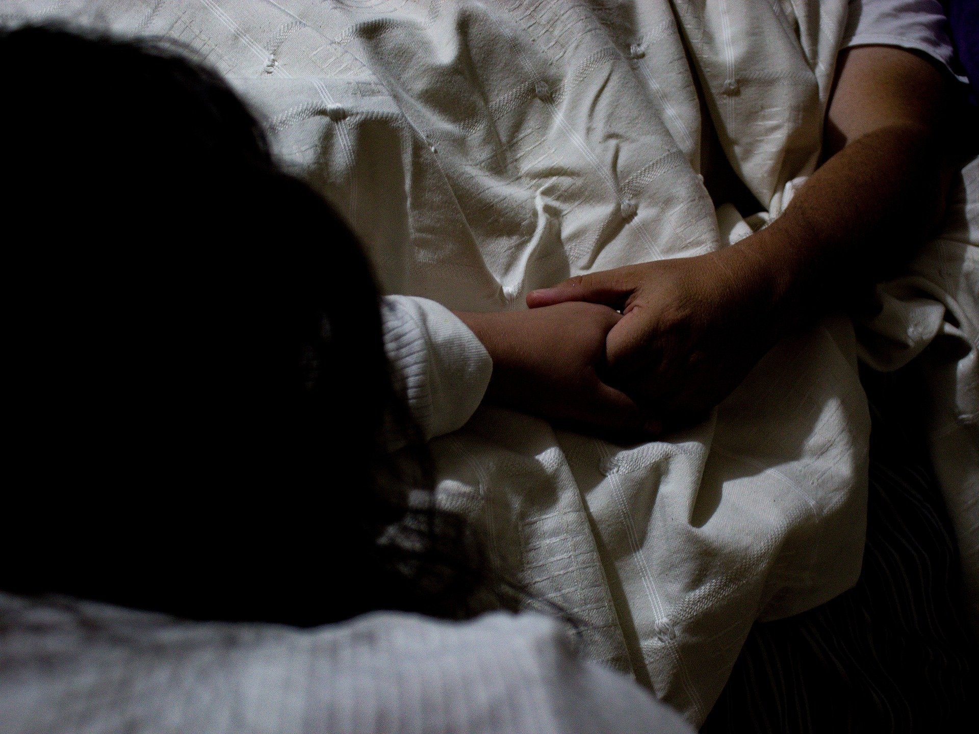 A man and woman holding hand while he lies in bed   Photo: Pixabay/Erubiel Flores