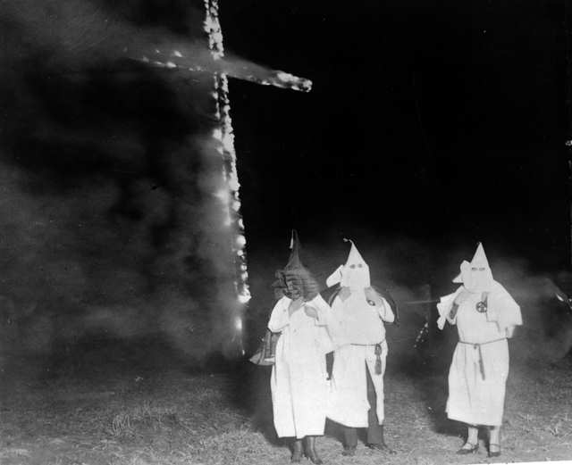 Ku Klux Klan members and a burning cross, Denver, Colorado, 1921.   Photo: Wikimedia Commons Images