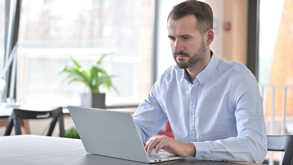 Man looking serious while on a laptop | Photo: Shutterstock/Stockbakery