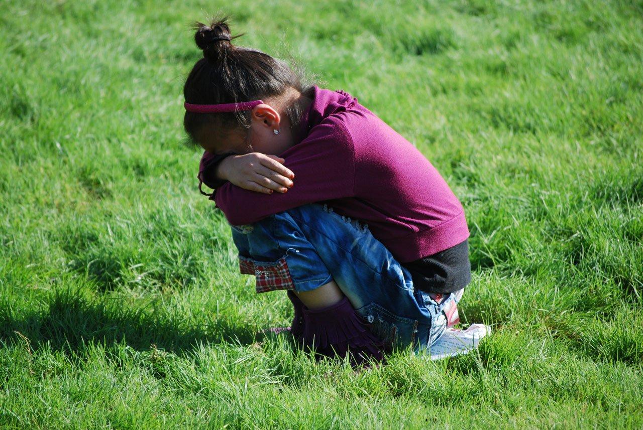 Niña agachada con el rostro escondido en sus rodillas. | Imagen: Public Domain Pictures