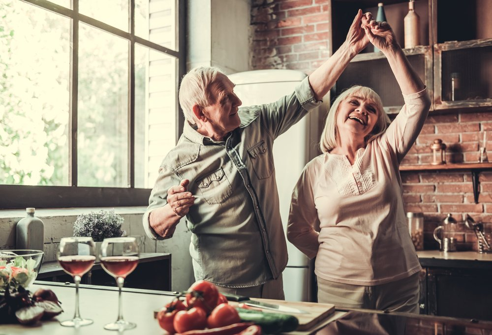 A photo of a senior couple dancing and smiling in the kitchen. | Photo: Shutterstock.