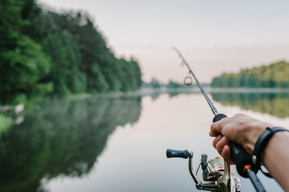 A man shows his fishing rod by the lake. | Source: Shutterstock