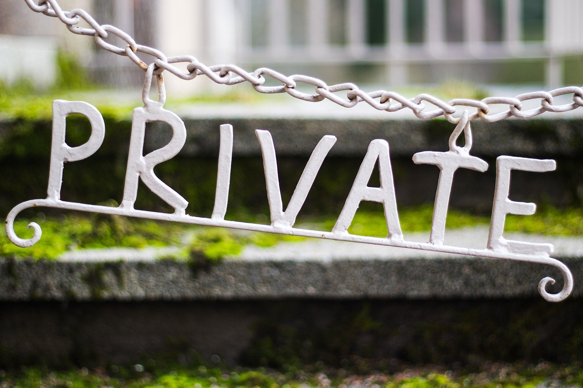 """A """"private"""" sign hanging from chains. 