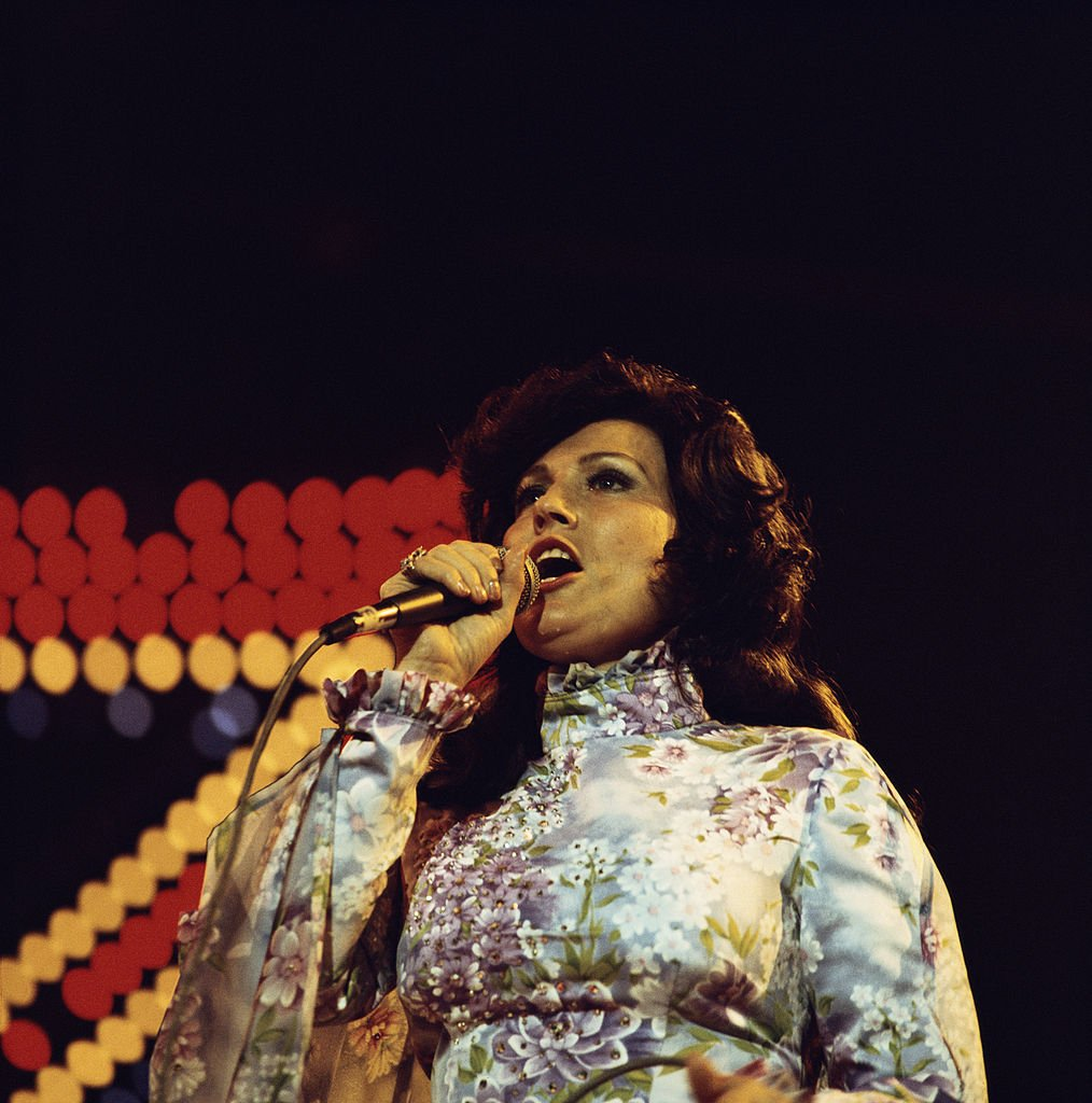 Loretta Lynn, U.S. country music singer-songwriter, singing into a microphone during a concert, circa 1970. | Source: Getty Images