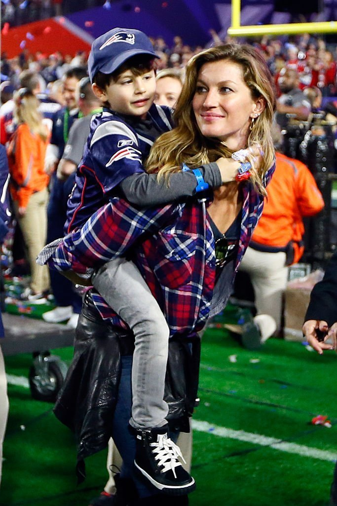 Gisele Bundchen, wife of Tom Brady #12 of the New England Patriots, walks on the field with their son, Benjamin after defeating the Seattle Seahawks during Super Bowl XLIX at University of Phoenix Stadium | Getty Images