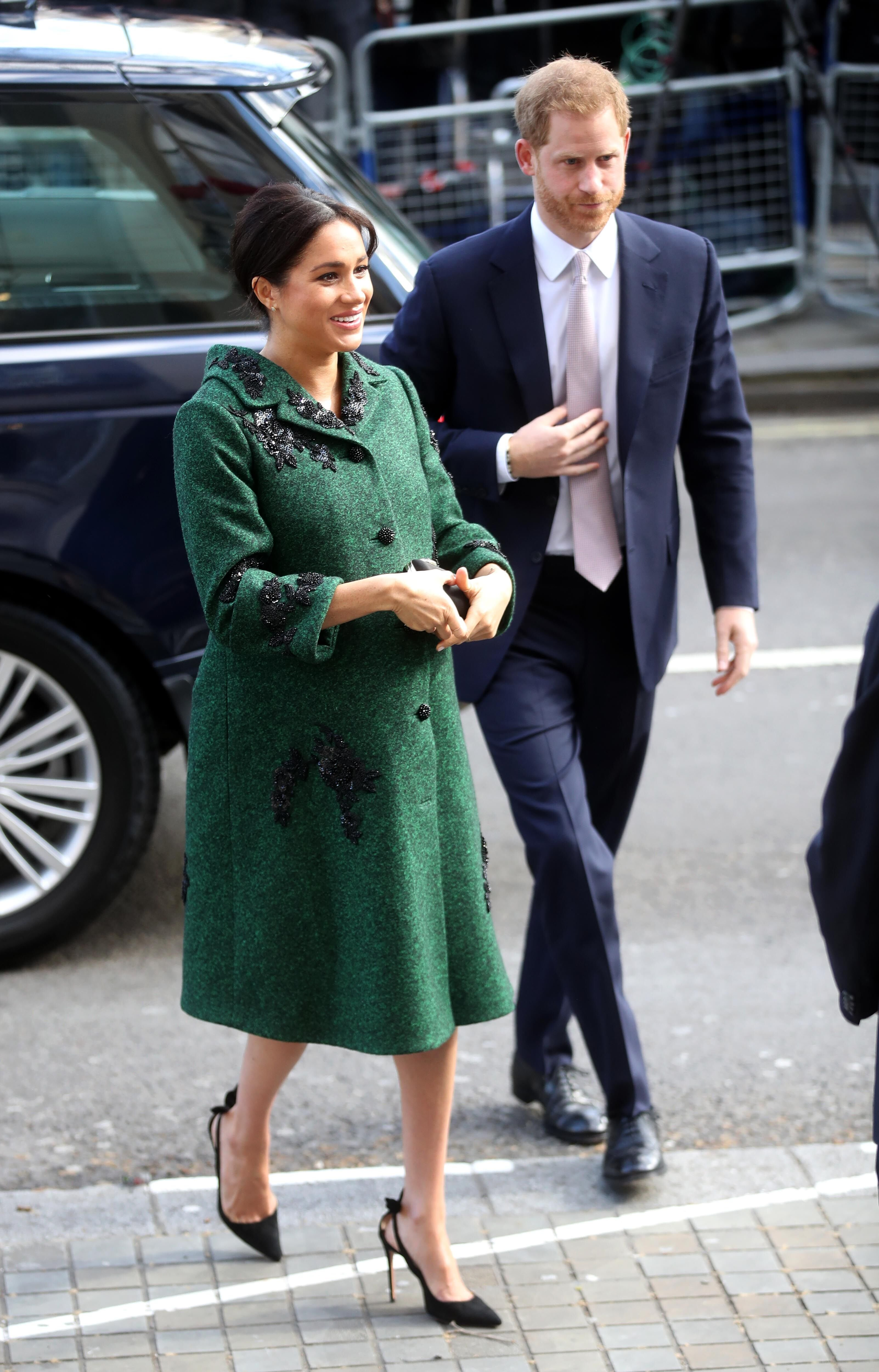 Meghan Markle walks with Prince Harry, in an emerald green coat. | Source: Getty Images