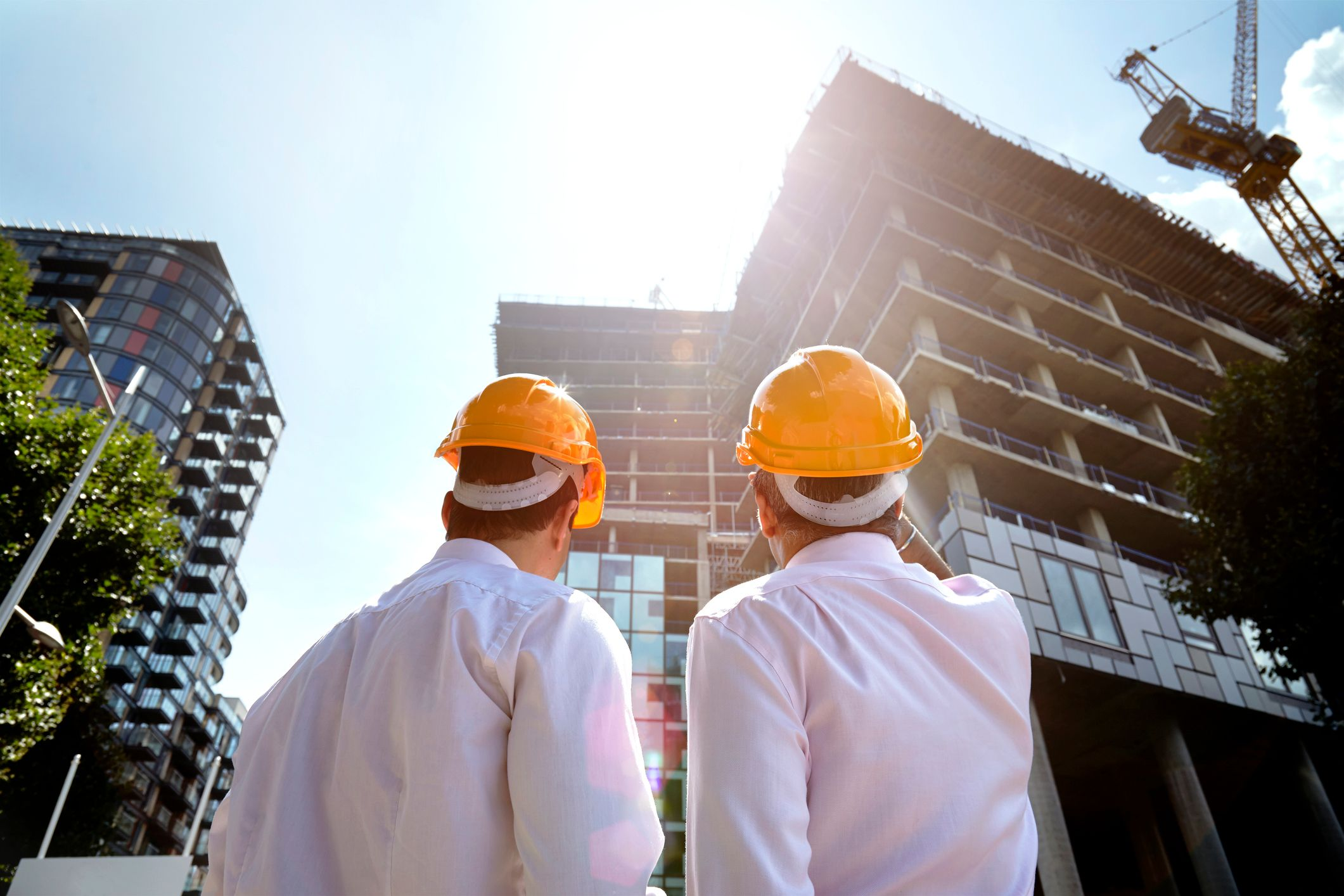 Two construction workers pointing at a building. | Source: Shutterstock