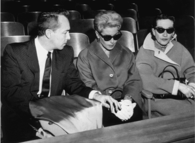 American actor Lana Turner (C), wearing dark sunglasses, sits next to her ex-husband, Stephen Crane, in a courtroom during the murder trial of their daughter, Cheryl Crane. Crane, who had stabbed Turner's gangster ex-boyfriend Johnny Stompanato, was acquitted for justifiable homicide.1958. | Source: Getty Images