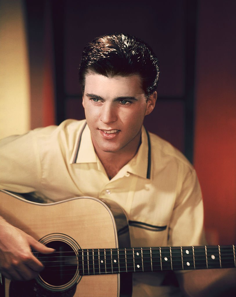 Ricky Nelson playing  a guitar as he  posed for a snapshot. | Source: Getty Images