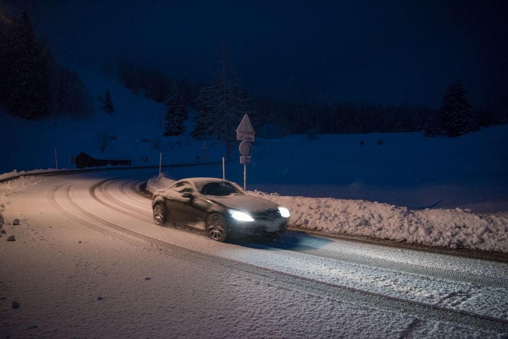 A car driving on the street while covered in snow. | Source: Shutterstock